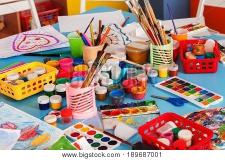 Kindergarten tables with painting brush and teacher in interior . Preschool class waiting kids. Playroom with a lot of object on table. Art room for education children's creativity. Top view