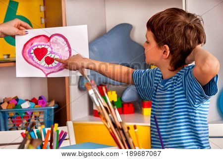 Small student boy painting heart in art school class. Child drawing by paints on table. Mother day holiday. Kid in a children's club. Craft drawing education develops creative abilities of children.