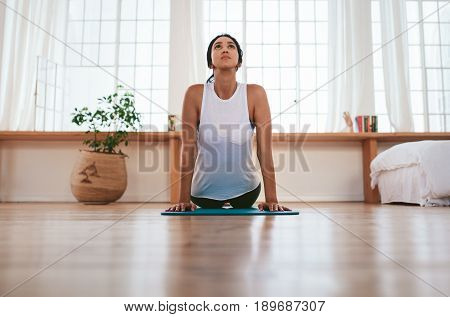 Beautiful fit woman practices yoga asana at home. Healthy female doing bhujangasana - cobra pose.