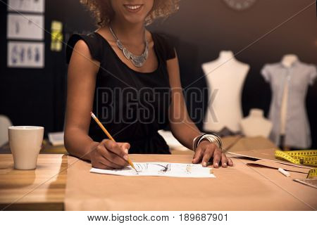 Portrait of a young fashion designer working on her atelier