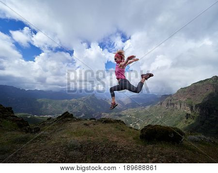 young happy woman jumping on top of the mountain, beautiful panoramic view