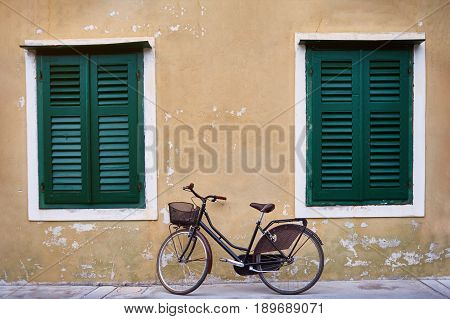 Bicycle with metal basket parked in front of an old wall of a house with flaked yellow plaster and big widows with green shutters.