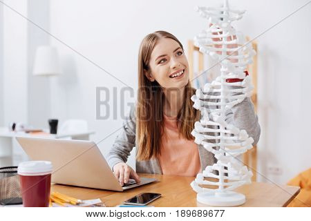 Enthusiastic learner. Lively intelligent motional lady studying the model of human genome while spending time in the classroom and working on her university project