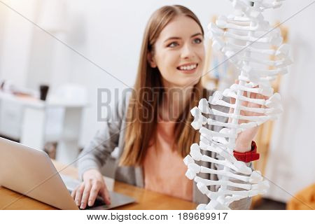 Human architecture. Productive committed ambitious lady looking excited while studying the model of human genome and getting ready with her assignment on genetics