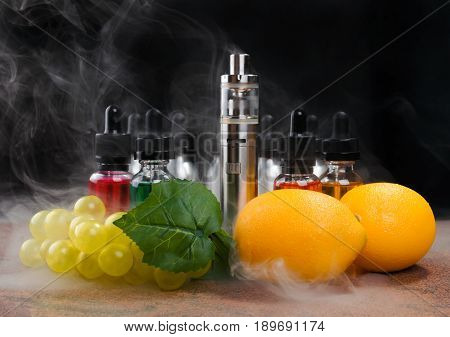 Electronic cigarette bottles with vape liquid lemons and fake bunch of grapes within vapor on granite surface and black background