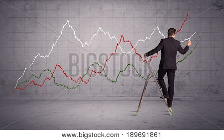 A guy in modern suit standing on a small ladder and drawing a chart on grey wall background with exponential progressing curves, lines