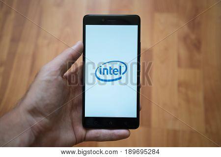 London, United Kingdom, june 5, 2017: Man holding smartphone with Intel logo on the screen. Laminate wood background.