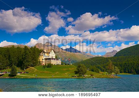 SANKT MORITZ SWITZERLAND AUG 21 2010: View on Hotel-Restaurant Waldhaus am See Alps at Sankt Moritzersee beautiful lake. Swiss lakes holidays vacations tours travels. Green hills. Matterhorn