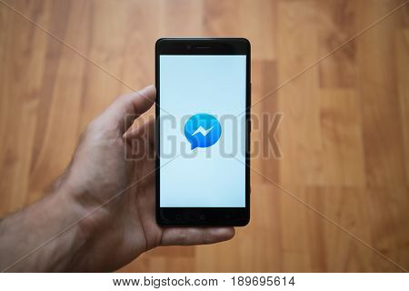 London, United Kingdom, june 5, 2017: Man holding smartphone with Facebook messenger logo on the screen. Laminate wood background.