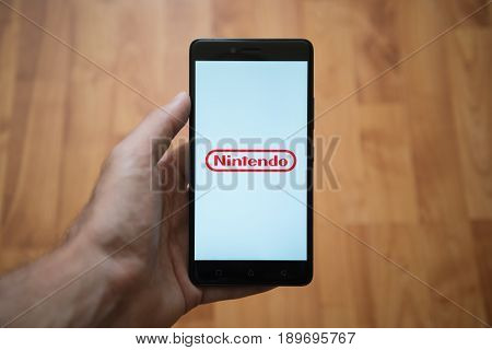 London, United Kingdom, june 5, 2017: Man holding smartphone with Nintendo logo on the screen. Laminate wood background.