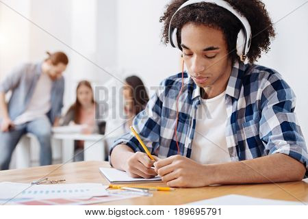 Inspiring sounds. Diligent focused handsome guy sitting at the table and writing down his ideas while listening to some music