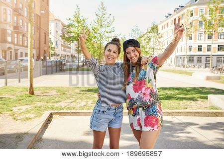 Two Cute Confidents Young Women Giving V-signs