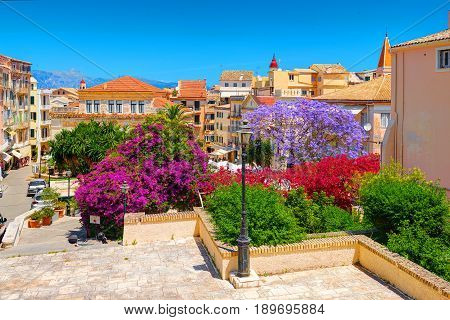 CORFU ISLAND, GREECE, JUN,06, 2014: Downtown garden park colorful trees flowers Greek old houses architecture of Greece Corfu island Kerkyra. Greece holidays vacation touristic tours. City garden park