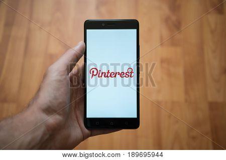 London, United Kingdom, june 5, 2017: Man holding Pinterest smartphone with  logo on the screen. Laminate wood background.