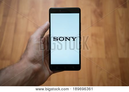 London, United Kingdom, june 5, 2017: Man holding smartphone with Sony LOGO on the screen. Laminate wood background.