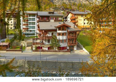 ZERMATT, SWITZERLAND, OCT,20, 2010: View on hotel chalet in Swiss cottage style on river Matter Vispa. Classic wooden chalet cottage. Matterhorn Alpine mountain. Swiss chalet. Swiss holidays vacations