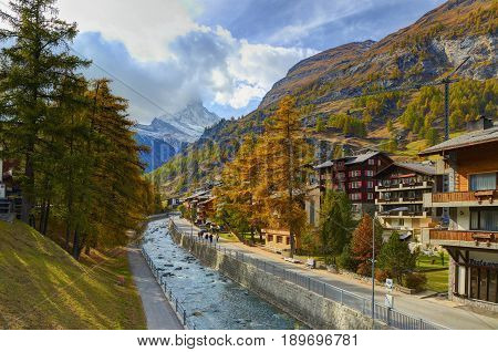 ZERMATT, SWITZERLAND, OCT,20, 2010: View on chalets in Swiss cottage chalet style on street Bachstrasse, river Matter Vispa and on Matterhorn and Alps mountain. Classic Swiss cottage chalet vacations