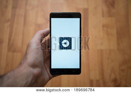 London, United Kingdom, june 5, 2017: Man holding smartphone with Uber LOGO on the screen. Laminate wood background.