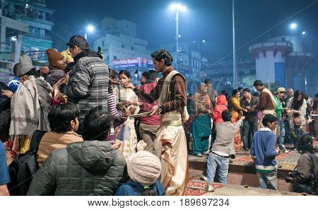 VARANASI, INDIA - JANUARY 3, 2016: Indian Brahmins offered prasad to poor people during Ganga Maha Aarti ceremony at Dashashwamedh Ghat in Varanasi, Uttar Pradesh, India