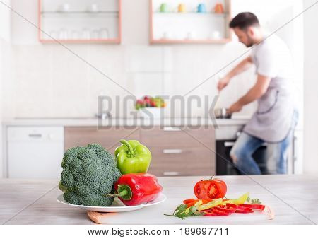 Colorful fresh vegetable on kitchen table with handsome man with apron cooking in background. Healthy groceries in focus