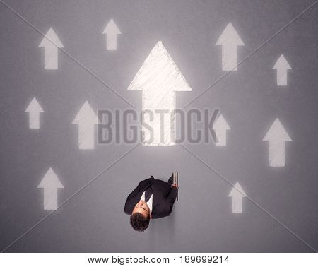 Young contemplating businessman stands in front of white arrows
