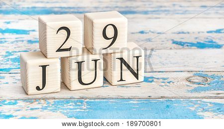 June 29th. Wooden cubes with date of 29 June on old blue wooden background.