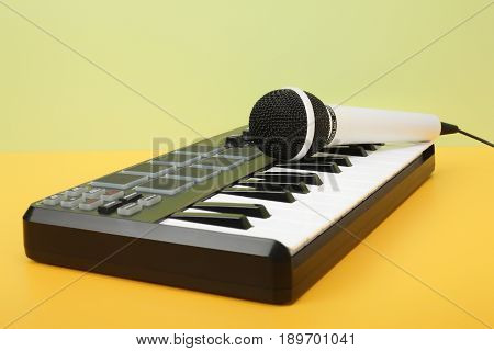 Musical instrument - MIDI keyboard and vokal microphone for a karaoke on a flavovirent background.