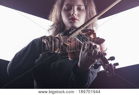Beautiful young woman playing the violin on dark background