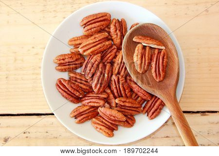 Pecan nuts on a white plate with a wooden spoon