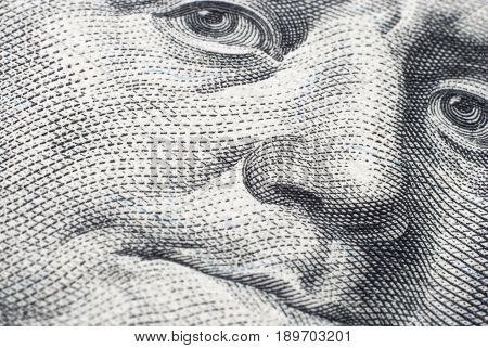 The face of Benjamin Franklin on a hundred-dollar bill close-up