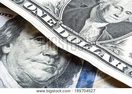A one-hundred dollar bill under a one dollar bill. One dollar over a hundred dollars