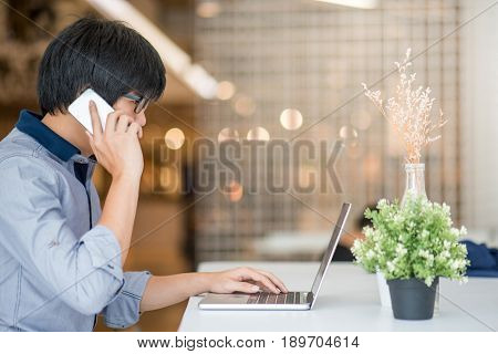 Young Asian man dressed in casual style working in coffee shop with his laptop computer and smart phone. Digital nomad and IT modern lifestyle work life balance concept
