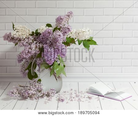 Beautiful bouquet of white and violet lilac flowers in glass vase with opened note-book on the white brick and wood background.