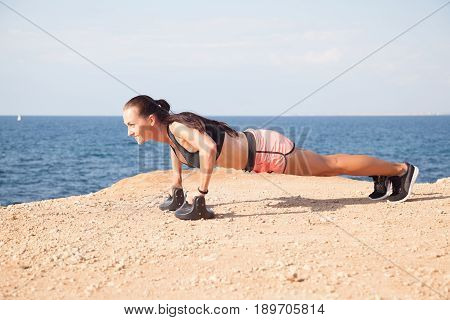Fitness Sports girl trains the muscles on the beach press-up 1