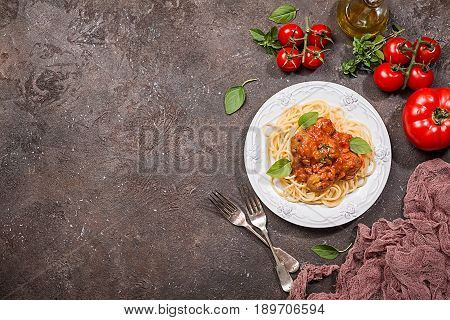Spaghetti pasta with meatballs and tomato sauce on white plate over brown background, top view