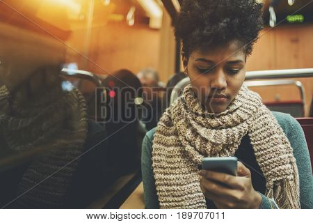 Pensive afro american student travelling home after study in evening and messaging with family via smartphone serious black teenage female with curly hair in train coach using her cell telephone