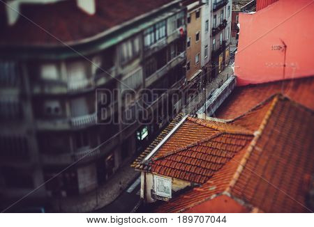 True tilt-shift shooting from hight point of small narrow street in central district of Lisbon Portugal during sunny summer day with old houses orange tiled roof and paving road