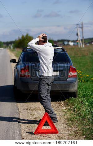 Frustrated brunet near broken car puts road sign on road