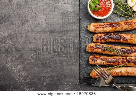 Grilled sausages with tomato sauce on dark background, top view
