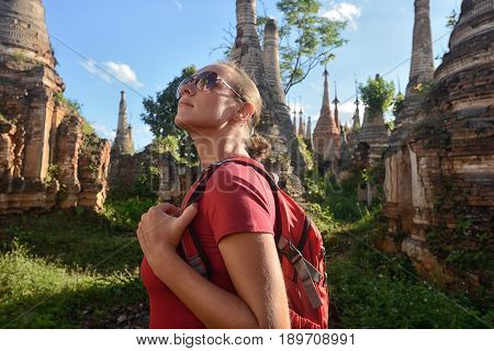 Traveler with a backpack looks at ancient Buddhist stupa of the temple complex InDein. Mayanmar