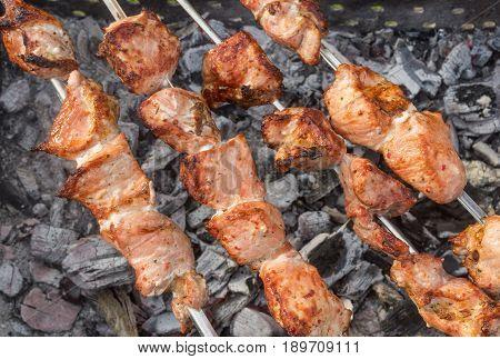 Pork meat cooking outdoor on skewers over smoldering carbon