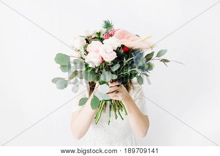 Pretty woman with beautiful flowers bouquet at white wall. Lifestyle composition.