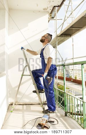 A construction worker in work attire and protective gloves enters a ladder with a drill in hand.