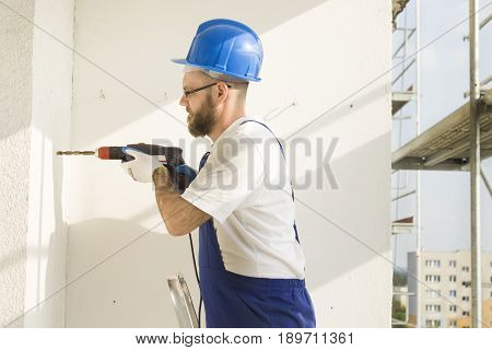 Construction worker in work attire, protective gloves and a helmet on site. Drilling the hole with a drill in the wall.