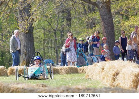 STOCKHOLM SWEDEN - MAY 21 2017: Concentrated little girl driving a home made soapbox car downhill on a field in the race Gardesloppet at Djurgarden Stockholm Sweden. May 21 2017