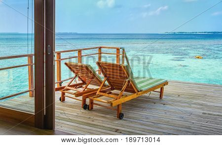 Two Wooden Lounge Chairs On The Deck Of Water Bungalow Suite Overlooking The Lagoon And Sea Horizon