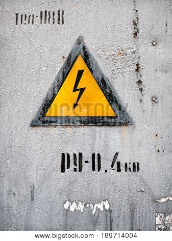 Electric shock hazard sign on rusty metal surface.