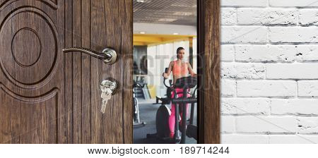 Opened door to gym or fitness club, woman exercise on elliptical training. Welcome to sport, healthy lifestyle concept