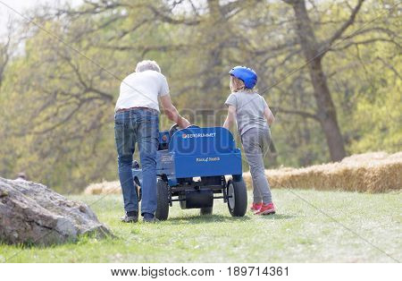 STOCKHOLM SWEDEN - MAY 21 2017: Rear view of granpa and grandchild push a soapbox car up the hill in the race Gardesloppet at Djurgarden Stockholm Sweden. May 21 2017