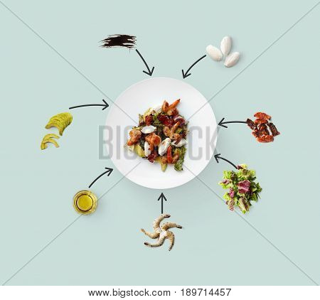 Seafood salad collage with ingredients, isolated on blue. King prawn, shrimps, lettuce, avocado, mozzarella and other ingredients near plate with dish